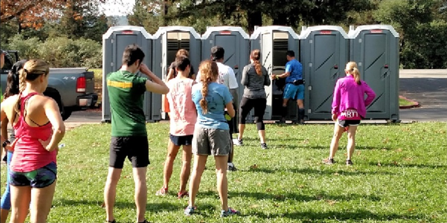 Porta-potties, like any other public restroom, are no risk to bare feet.