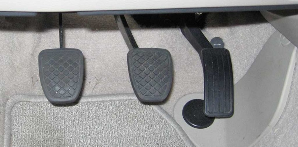 Typical floorboard and pedals of a manual transmission vehicle. The rough treads of the pedal pads help prevent any foot slippage. Bare feet will grip and hold onto to pedals better than any footwear could.